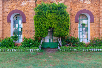 Orange colored bricks stone wall with two big old grunge windows and closed grunge door with green metal grid framed by two green bushes in sunrise time at Montaza public park, Alexandria, Egypt