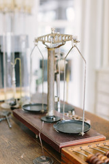 Vintage pharmaceutical scales on an old wooden table with other pharmaceutical supplies