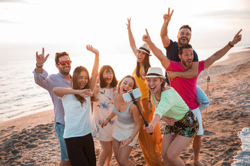 Happy multiracial young people are making a selfie at the beach while they are in a summer party. Friends and holiday concept