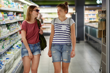 Positive young female costumer teenagers have stroll in supermarket, dressed in jean short and t shirts, carry bags, enjoy conversation, buy necessary products, prepare for party with friends