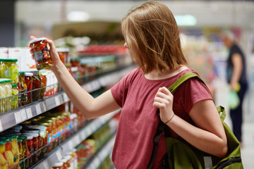 Sideways shot of pretty young femake customer holds canned goods in glass container, stands in food store, dressed in casual clothes, carries her rucksack, chooses canned vegetables for supper