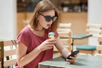 Serious pretty young European female with bobbed hairstyle, wears shades, downloads photos in internet, uses modern smart phone for online communication, eats fruit ice cream, recreats in cafeteria