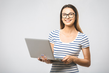 Portrait of happy young beautiful surprised woman standing with laptop isolated on white background. Space for text.