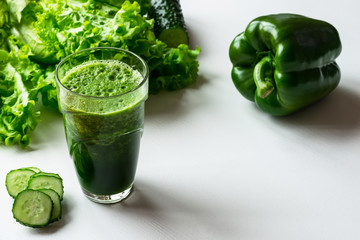 Glass of green vegetable smoothie on white background. Copy space.