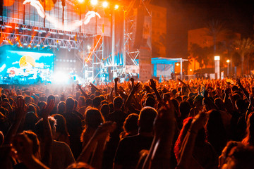 View of a concert with people or audience with hands in the air and clapping at a music festival. Summer music festival.
