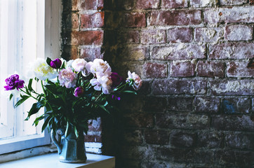 Peonies on a window sill in loft style room with copy space on brick wall