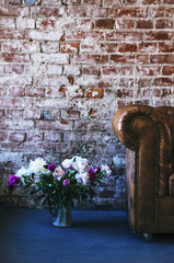 Loft interior details - leather sofa, bunch of flowers, brick wall and rough floor