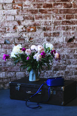 Colorful peony and vintage suitcase in loft interior space