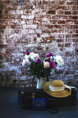 Travel inspiration - bunch of peony flowers, vintage suitcase and straw hat in loft style interior