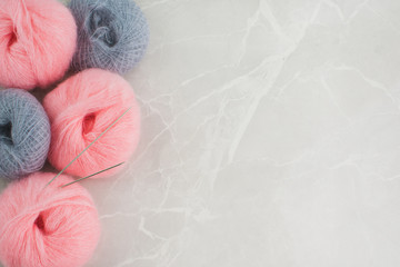 Pink and grey fluffy yarn balls on the left side of a marble background.