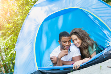Intimate Multiethnic Young Adult Couple Camping and Laying In Tent