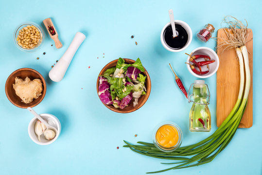 Summer lettuce with salad dressing vinaigrette on blue