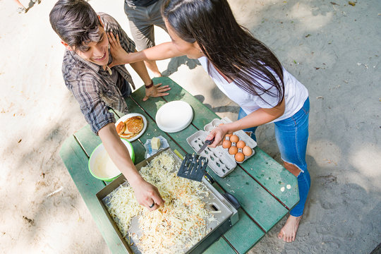 Multiethnic Young Adult Couple Having Fun Cooking At The Campground