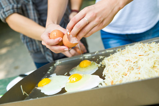 Young Adult Couple Cracking Open and Cooking Eggs and Potatoes At The Campground