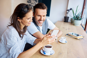 Couple looking at phone together while having coffee in cafe
