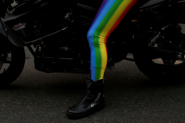 A person wears rainbow colored leggings o a motorbike before the 2018 New York City Pride Parade in Manhattan, New York