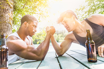African American Man Arm Wrestling With Mixed Race Man Outdoors