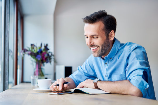 Man looking at phone and writing in calendar while out for coffee in cafe