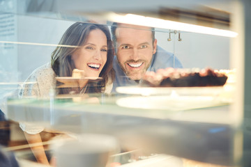 Cheerful couple choosing cake while spending time in cafe together