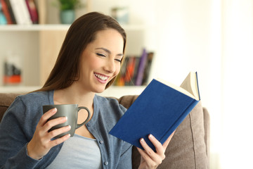 Happy woman reading a paper book alone at home