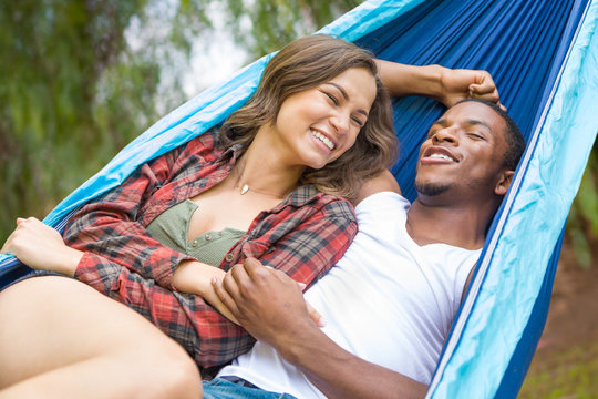 Affectionate African American Man with Hispanic Girl Laying in Hammock Outdoors