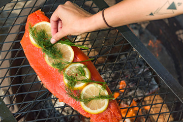 Woman Adds Herbs to Fillet Of Salmon and Lemon Slices on Outdoor Grill