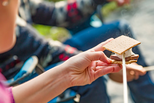 Closeup of Hands Building Smore with Roasted Marshmallow and Chocolate At Campfire Outdoors