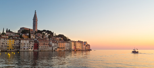 Colorful sunset of Rovinj town, Croatian fishing port on the west coast of the Istrian peninsula. Colorful evening seascape of Adriatic Sea. Traveling concept.
