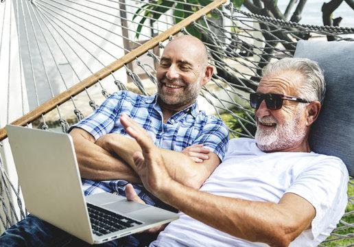 Senior men lying on a hammock using a laptop