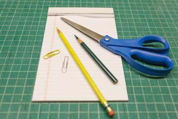 Office and school supplies on a green cutting mat