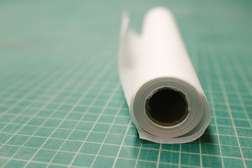 Roll of exam table paper on a green cutting mat