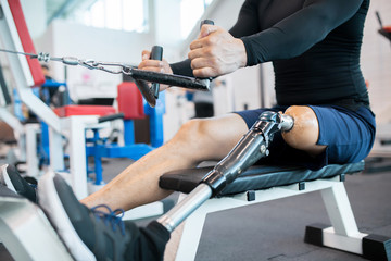 Low section closeup of unrecognizable muscular man with prosthetic leg using weight machines while working out  in gym, copy space