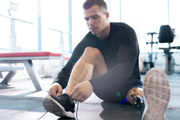 Full length portrait of muscular sportsman with prosthetic leg tying shoe sitting on floor in modern gym, copy space