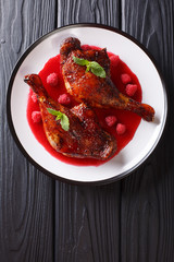 Delicious food gourmet: fried duck legs served with raspberry sauce and mint on a plate. Vertical top view