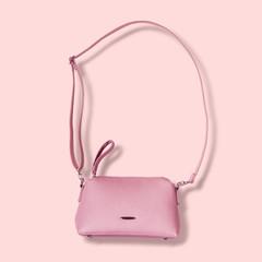 Ladies pink pastel handbag with long strap on pink background