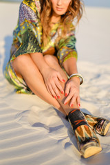 Young woman wearing green beach robe and having red nails sitting on sand. Concept of beach photo session and summer.