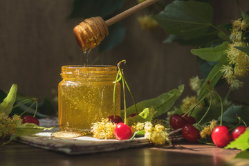 Open glass jar of liquid honey and honey dipper, bunch of linden flowers