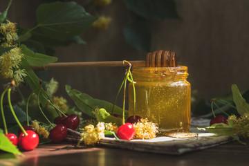 Open glass jar of liquid honey and honey dipper, bunch of linden flowers