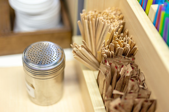 Wooden table with coffee self service acessories. Wooden sticks for stir, sprinkle chocolate can and sugar