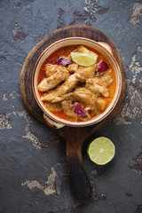 Massaman curry with chicken meat on a rustic wooden serving board, view from above on a brown stone background, vertical shot