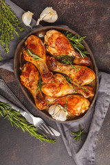 Grilled spicy chicken legs baked with garlic, rosemary and thyme on dark background.