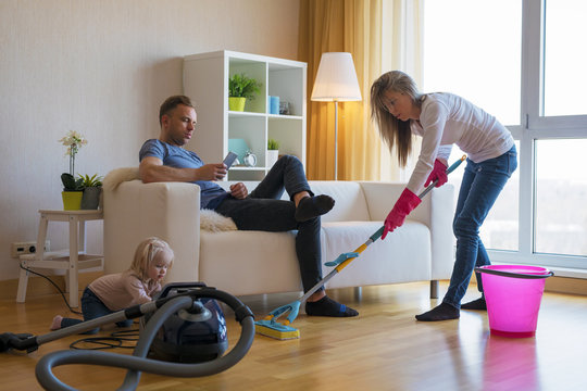 Woman cleaning floors at home while her lazy man sitting in couch