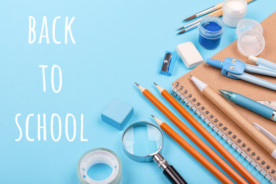 School stationary on blue background with inscription BackTo School. Notebook, pens, pencils and other tools.