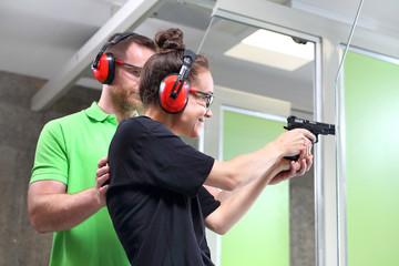 Szkolenie strzeleckie. Kobieta strzela z broni na strzelnicy pod okiem instruktora.