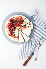 Homemade cheese cake with berries on white wooden table with towel, knife and fork. Top view. Red currant, black currant and cherry.