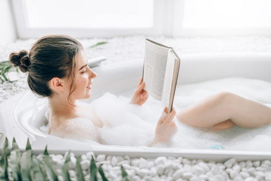 Woman lying in bath with foam and reads magazine