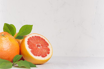 Fresh glossy whole grapefruits and round slice with green leaves on white wooden background with copy space.
