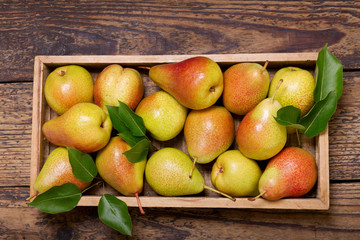 pears with leaves in a box on wooden table, top view