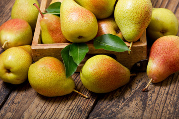 pears with leaves in a box on wooden table