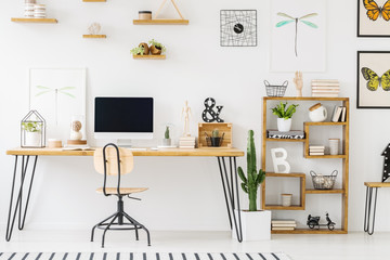 Real photo of a simple home office interior with a desk, computer, chair, cupboard, cactus, posters with dragonflies and butterflies on the wall. Place your product on the empty screen
